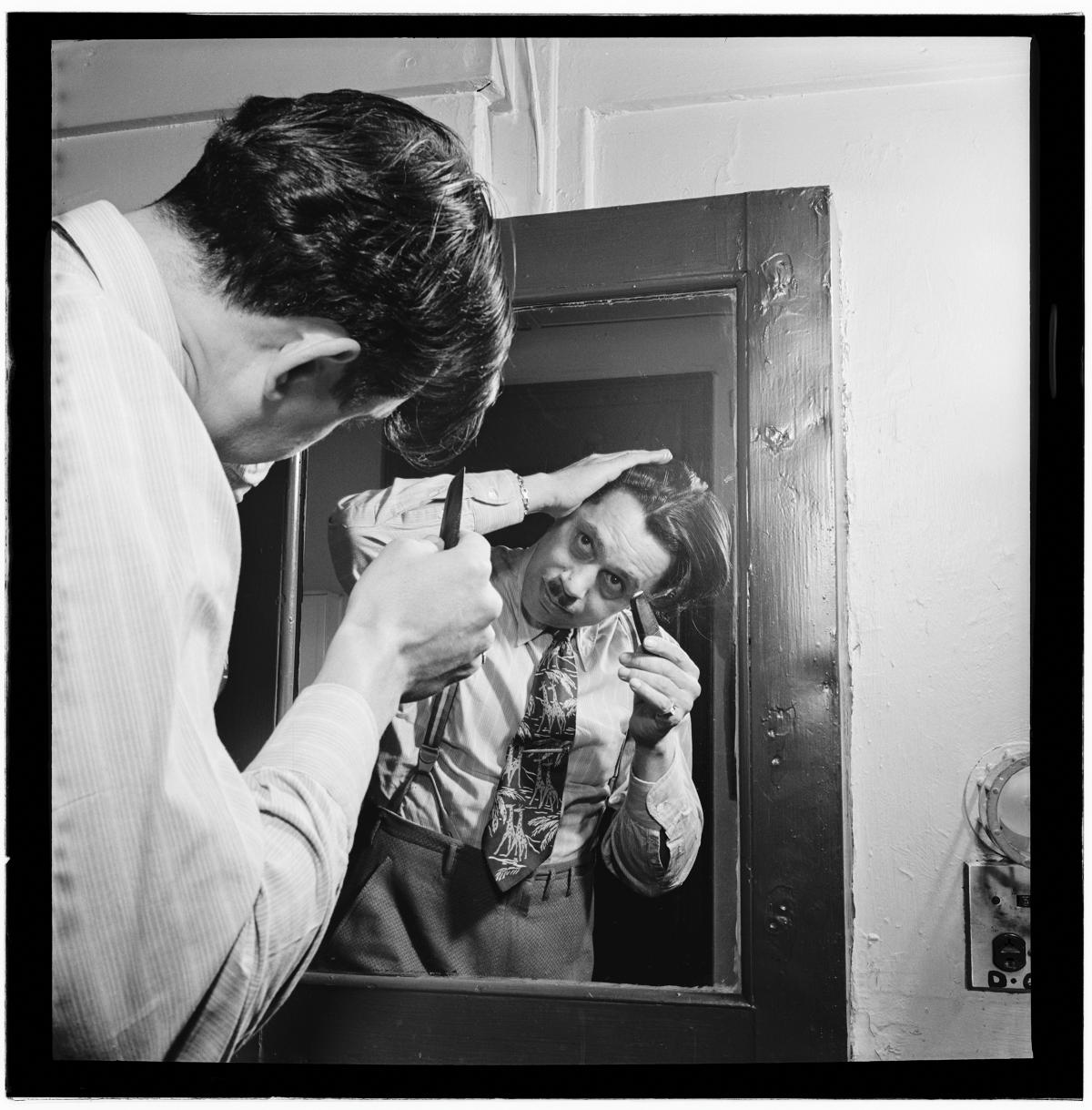Calloway, looking into a mirror with his back to the viewer, shaving