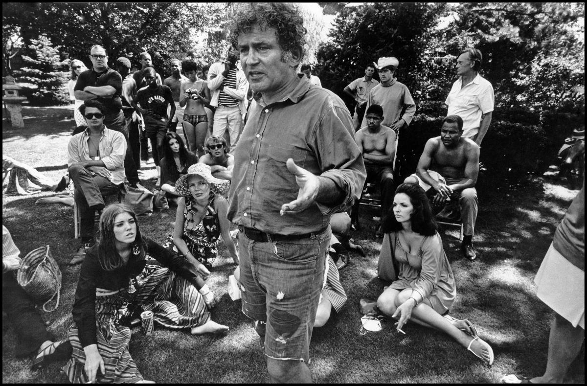 a white man stands and talks to a crowd of hippies