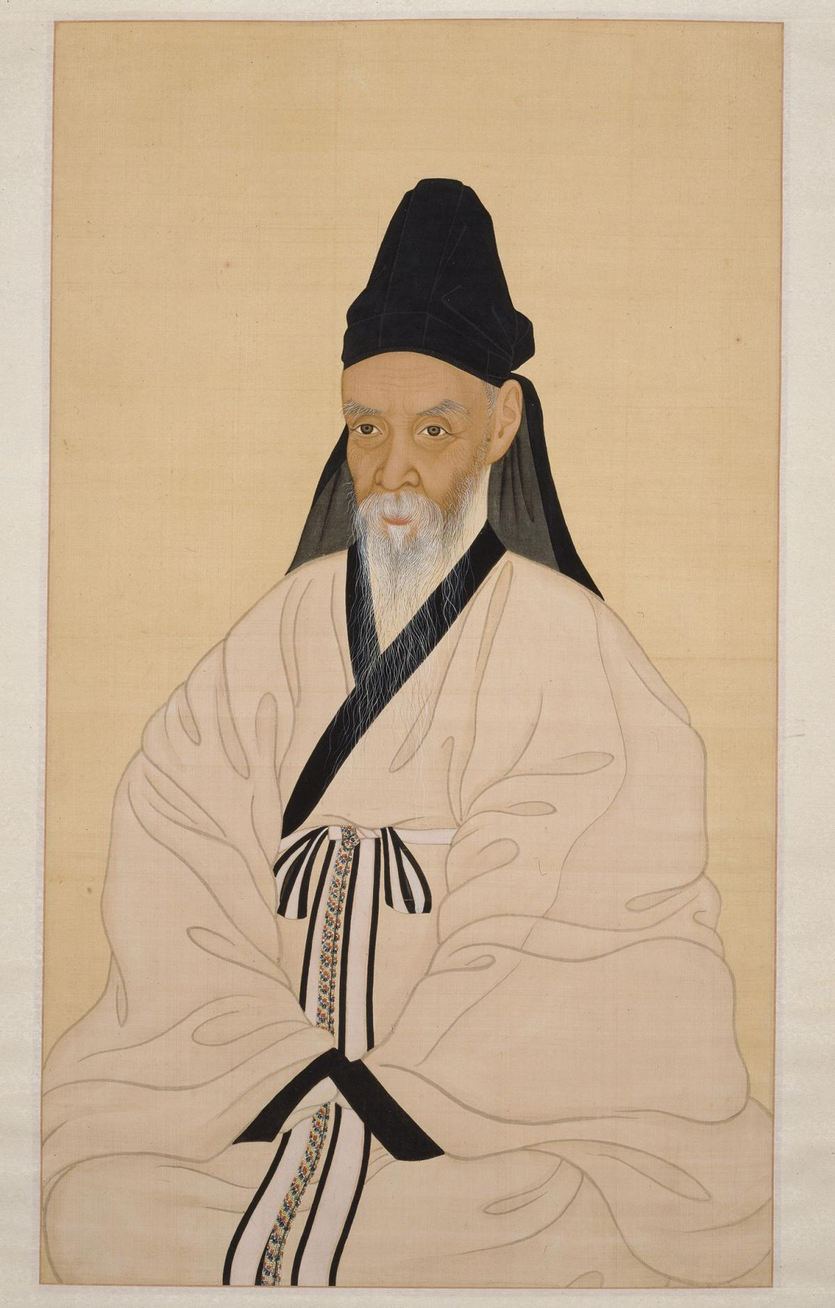 Yi Jae in a white robe, seated with hands folded in his lap, wearing a black cap