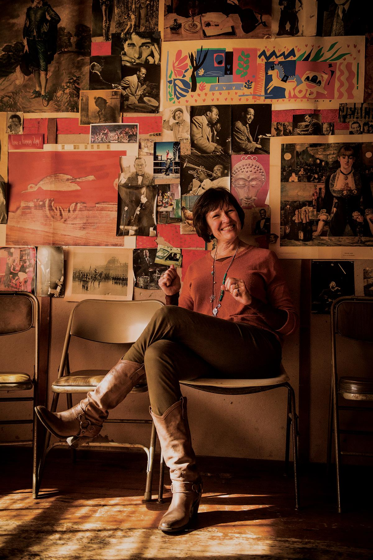 Susan Shillinglaw sitting with her legs crossed, in a room wall papered with photgraphs