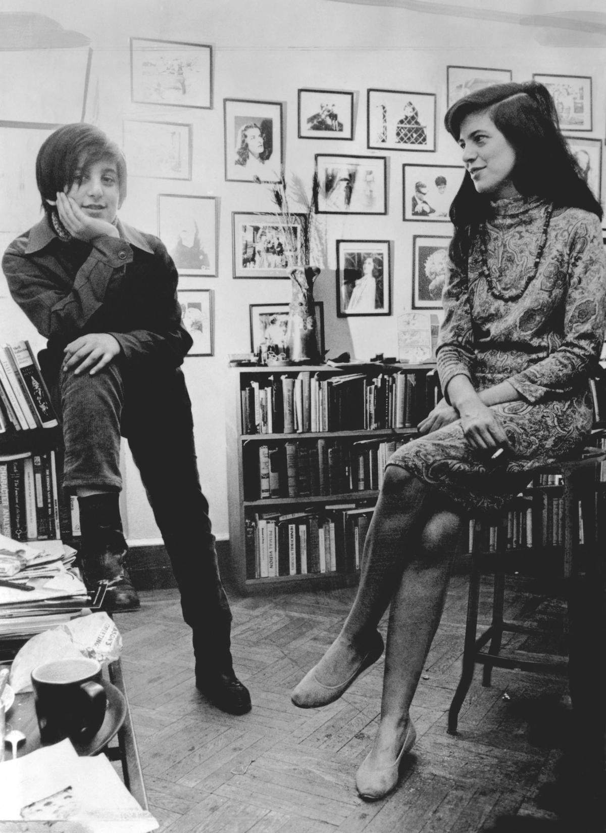 Sontag, seated on a stool, looks at her young son while he rests his hand on his chin