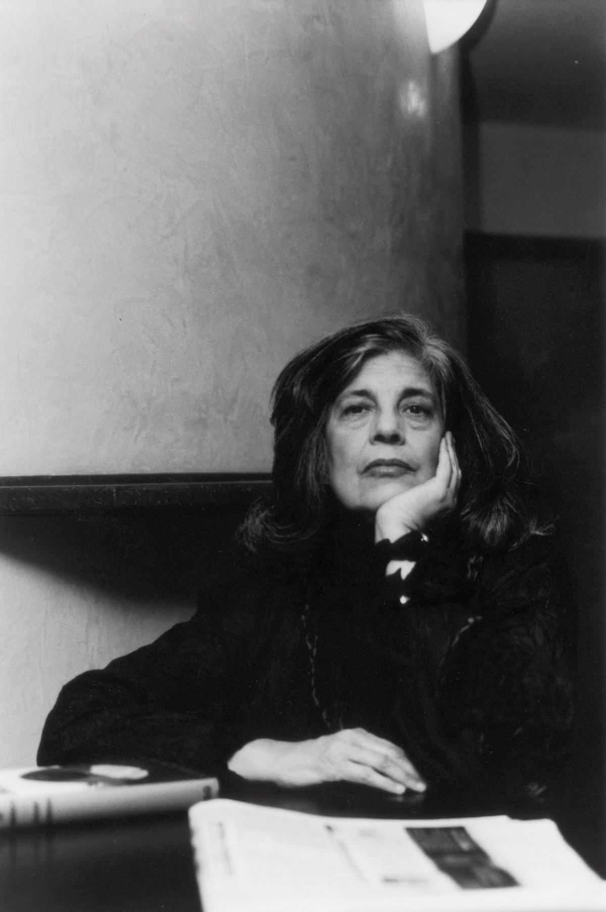Sontag resting her chin in her hand, seated at a desk