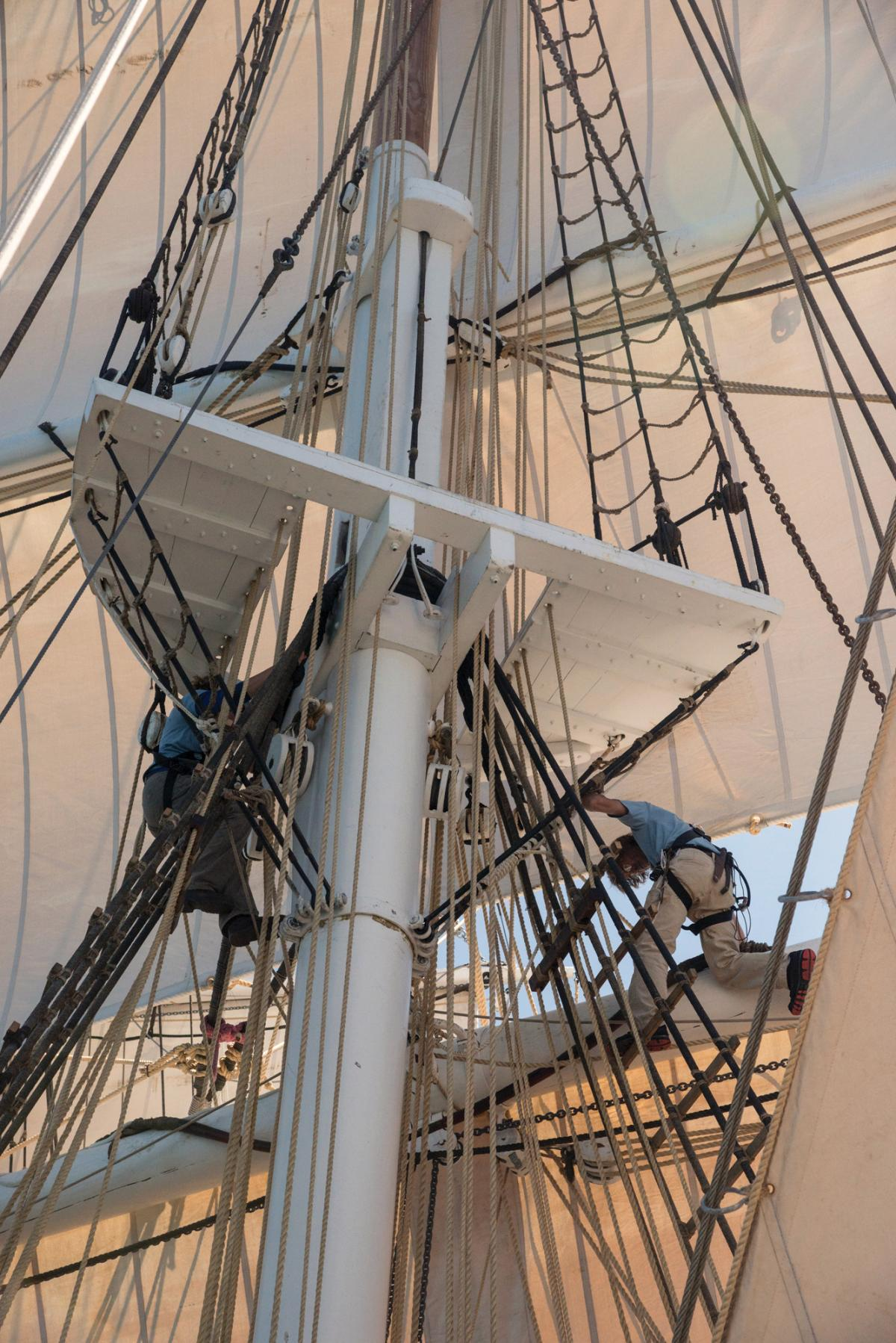 Deckhands climb up into the ropes of the rigging