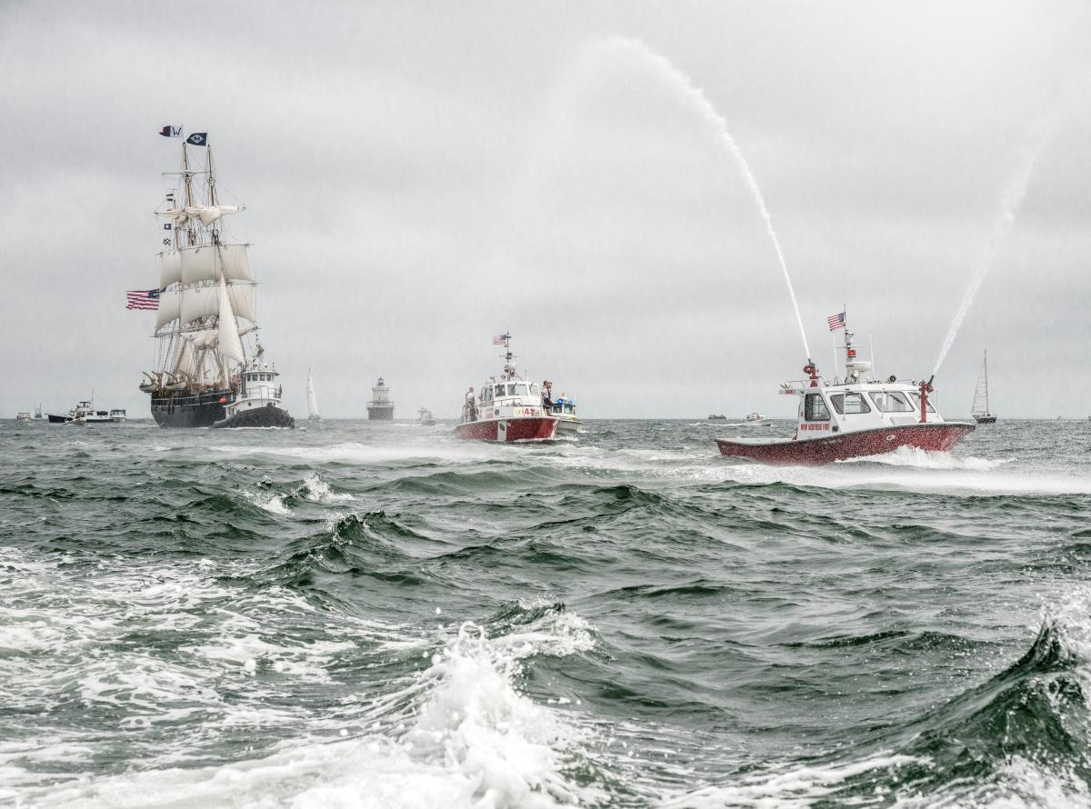 Fireboats and the Morgan on a choppy sea, with grey skies