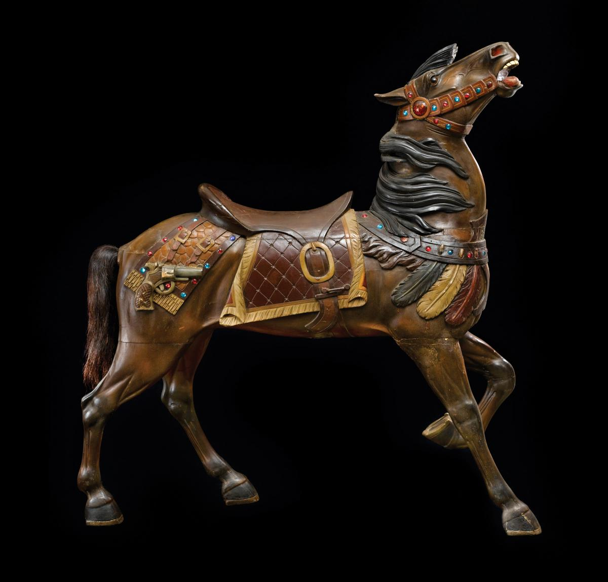 A wooden carousel horse with a raised head, made by Charles Carmel. Done in brown wood, wearing an elaborate saddle and halter