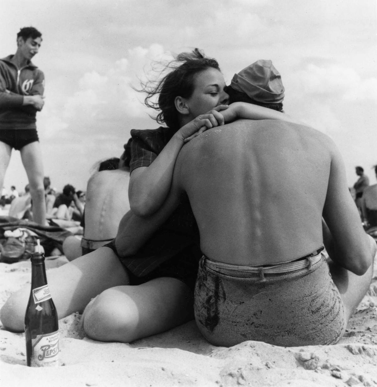 Black and white photo of a man and woman embracing on the beach at Coney Island, with the man's back to the viewer and the woman whispering in his ear