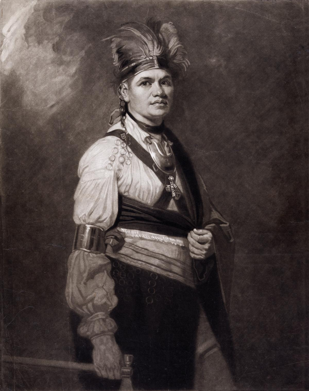 Joseph Brant, wearing a feathered Native American headdress and adornments, but also European-style shirt and trousers