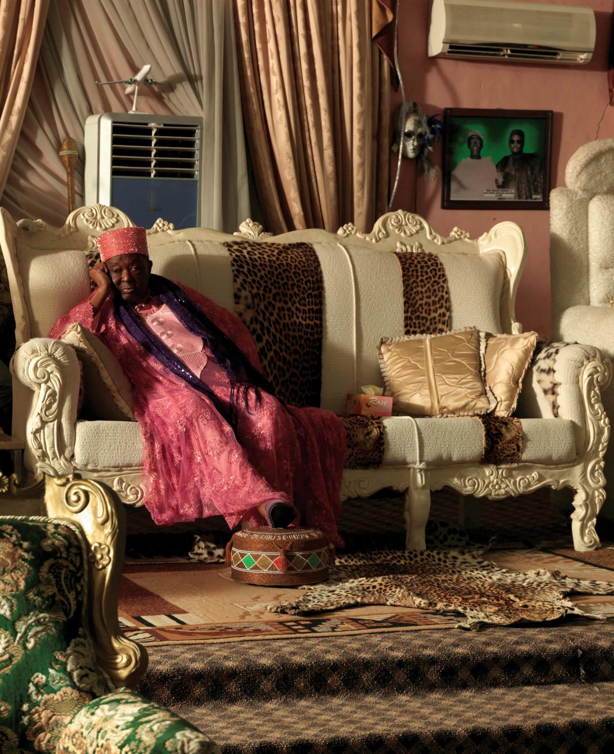 HRM Alayeluwa Oba Okunade Sijuwade, the Ooni of Ife, seated on a couch, wearing traditional, red robes, head resting on his hand