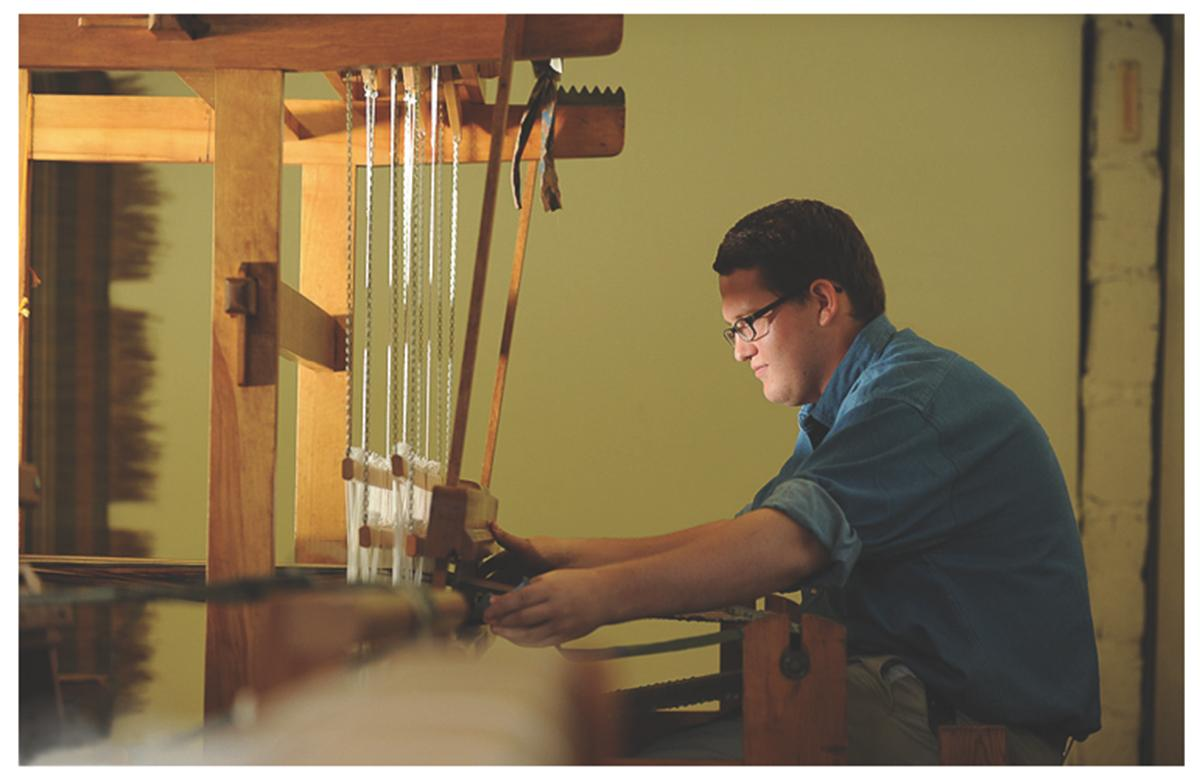 A student works at a wooden loom