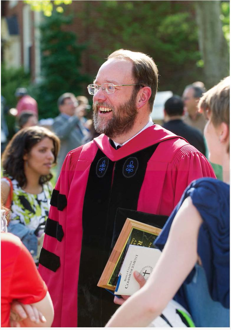Professor Foster wearing commencement robes, walking down the graduation aisle