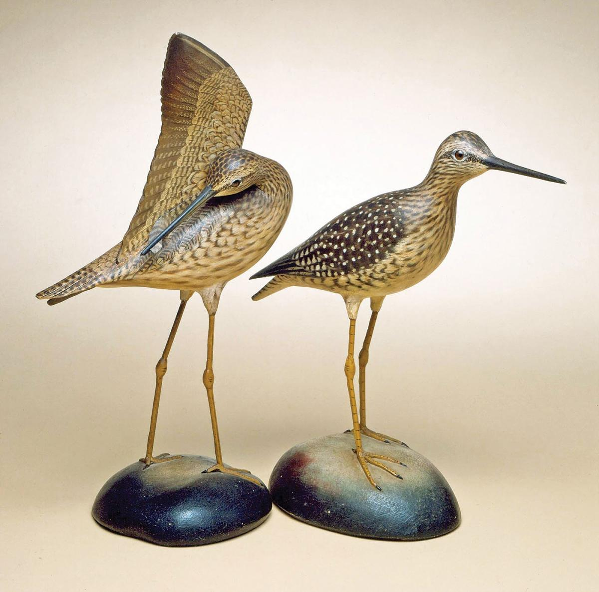 A pair of yellowlegs birds, carved in wood, one standing and the other reaching its beak under its wing