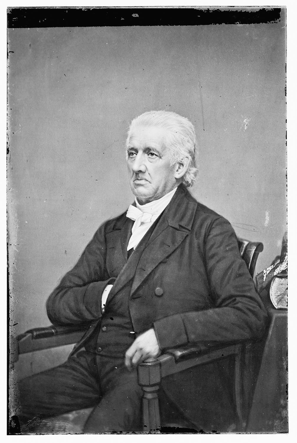 black and white photo of Lyman Beecher, wearing a black suit and white cravat, seated with his hand in his pocket