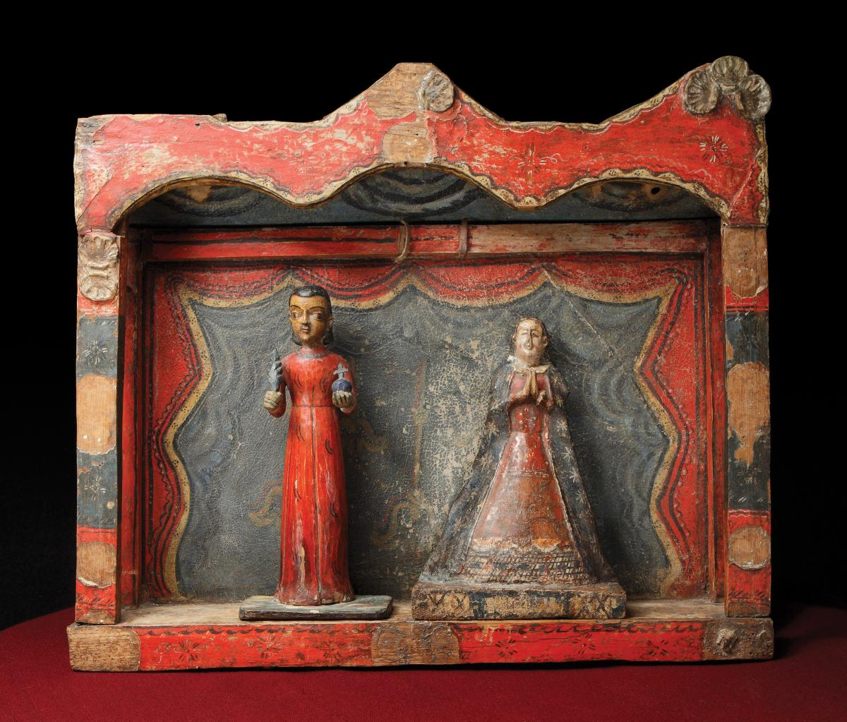two wooden figures of saints, framed in a red wood