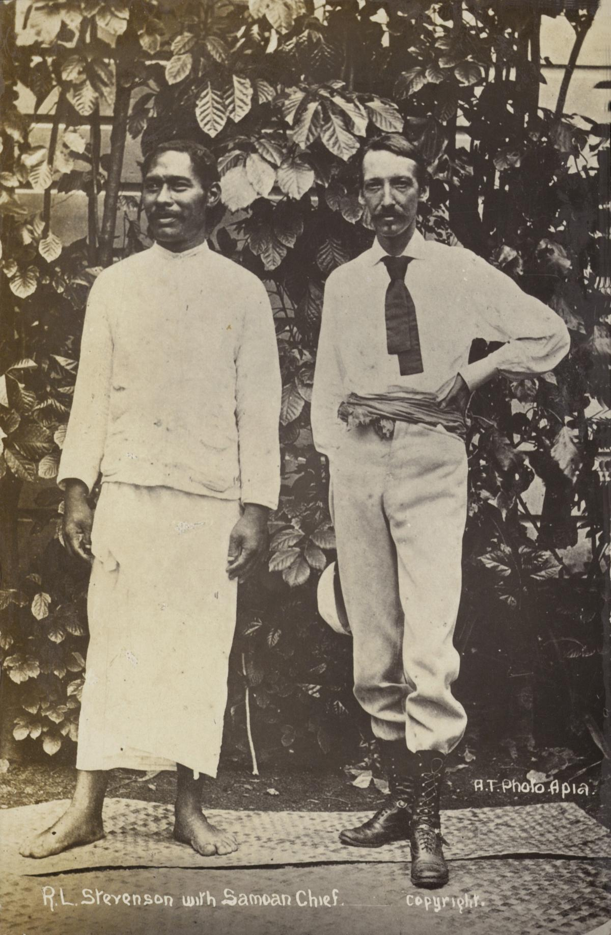 Black and white photo of Stevenson in a white shirt and hand on his hip, standing next to a Samoan chief, who is dressed in traditional white Samoan clothing