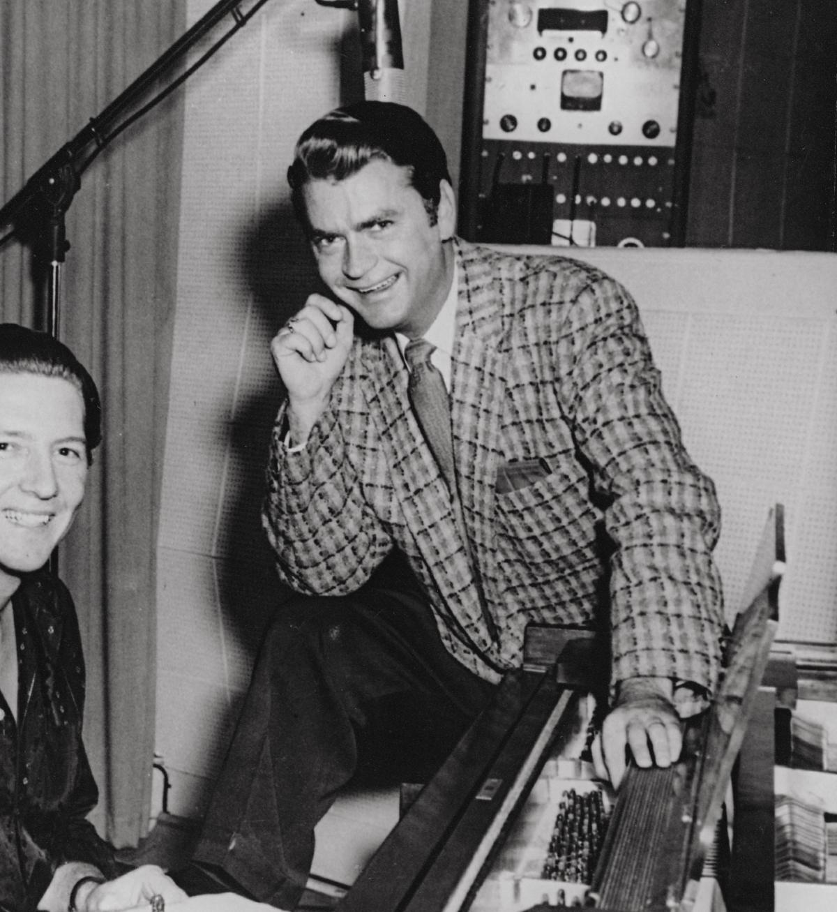 Sam Phillips in a checkered suit, resting his chin on his hand