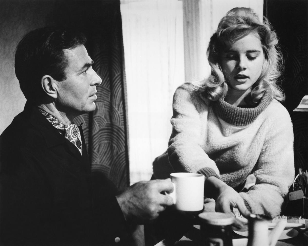 Black and white film still of a young girl and a man at a table