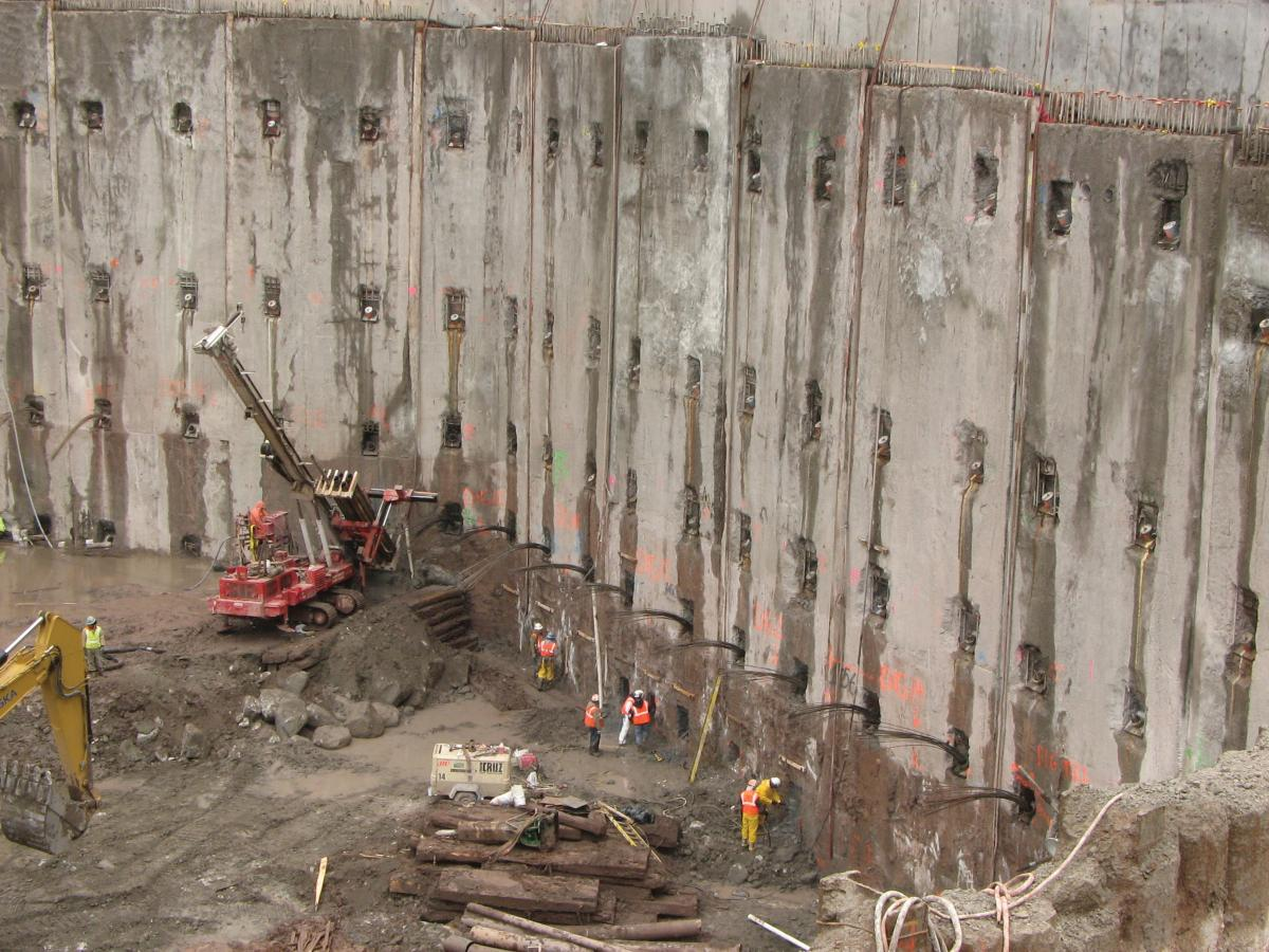 Photograph of a large cement wall with construction equipment