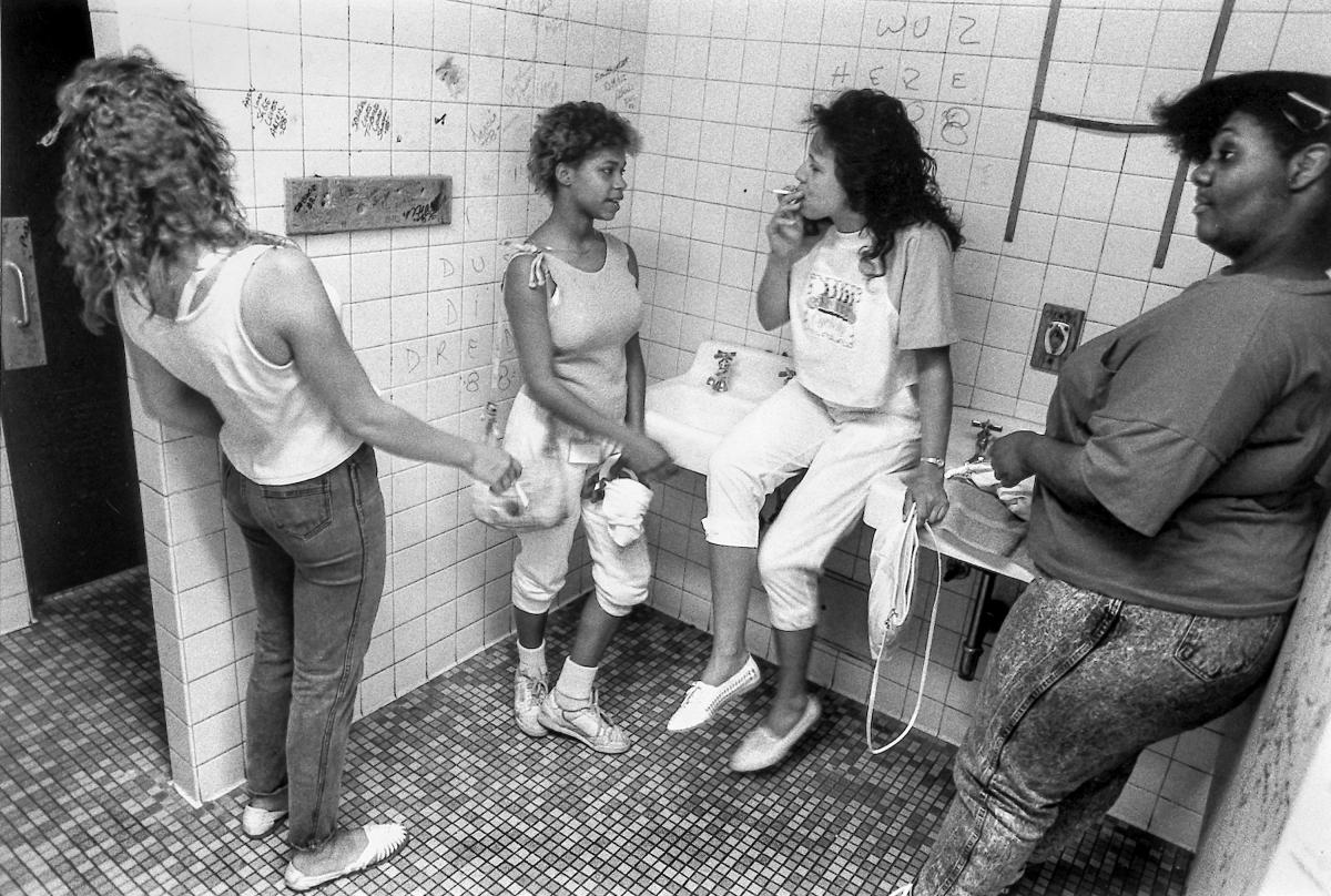 Black and white photograph of four girls in a high school bathroom