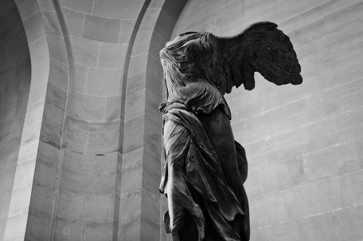Black and white photo of a winged statue with no head, viewed from afar.