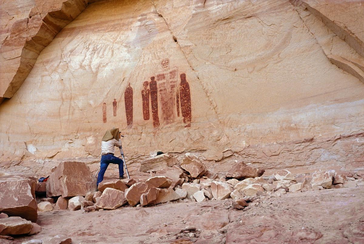 photograph of a man looking at a cave painting