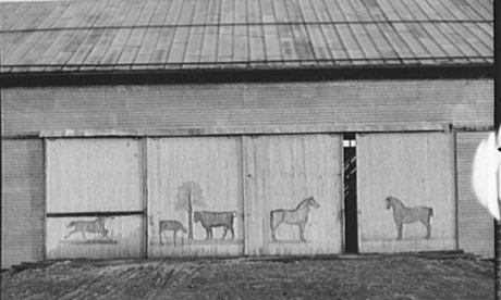 black and white photo of a barn with horses painted on doors