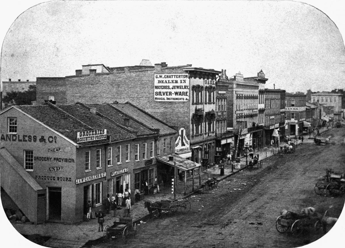 Black and white photograph of buildings in downtown city block, 1869