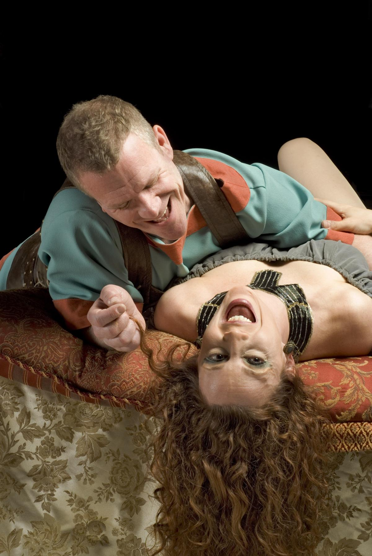 Photograph of man and woman laying down, woman's head thrown back, both laughing