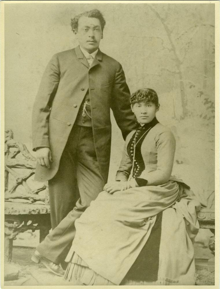 Mingo stands, with his hand on his seated wife's shoulder, both dressed in their wedding clothes