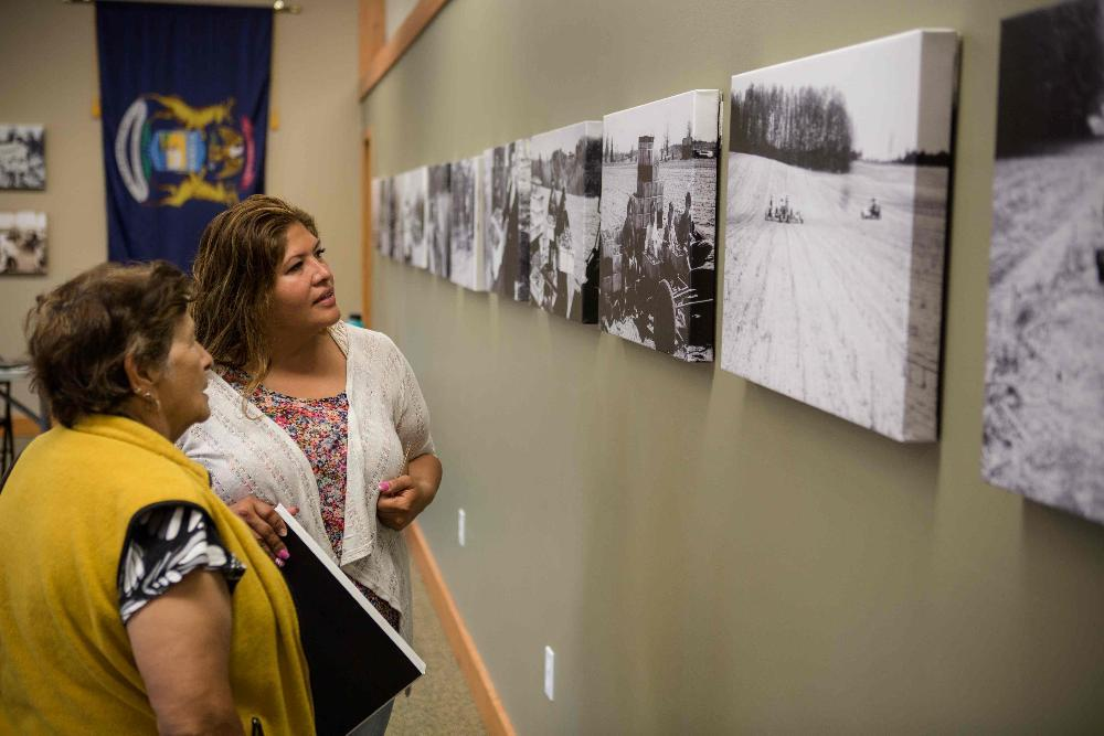 Attendees at a public exhibit discuss historic agricultural photographs.