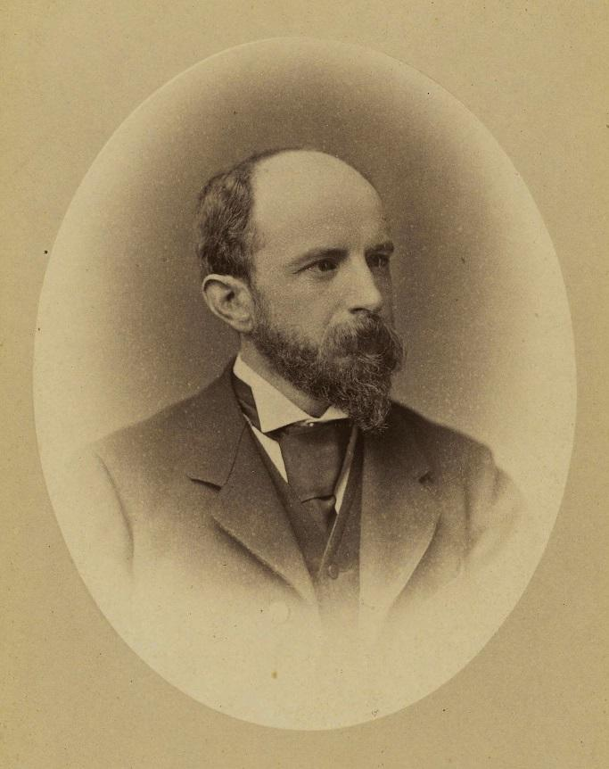 Sepia photograph of Adams, in a suit, with a beard and mustache