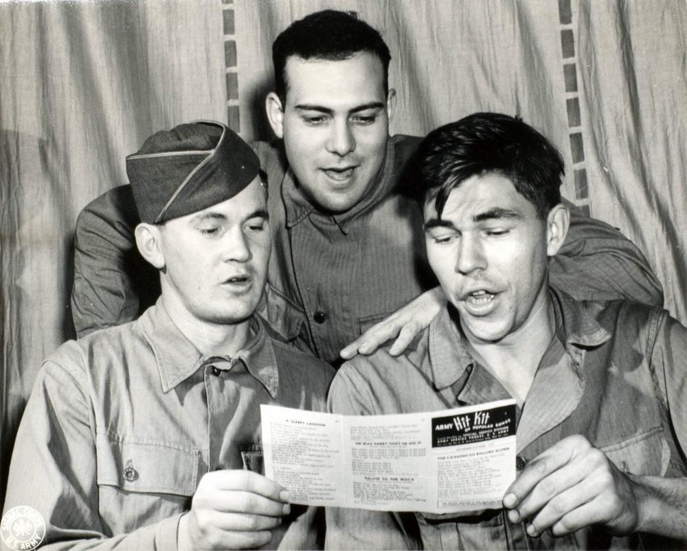 Three soldiers share a paper of the hit kit and sing along