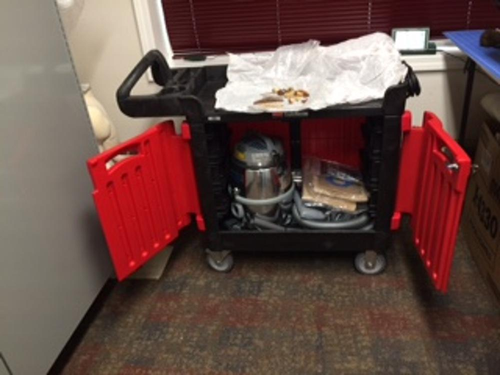 Collections Cleaning Cart in use, showing locked cabinet for Nilfisk vacuum.