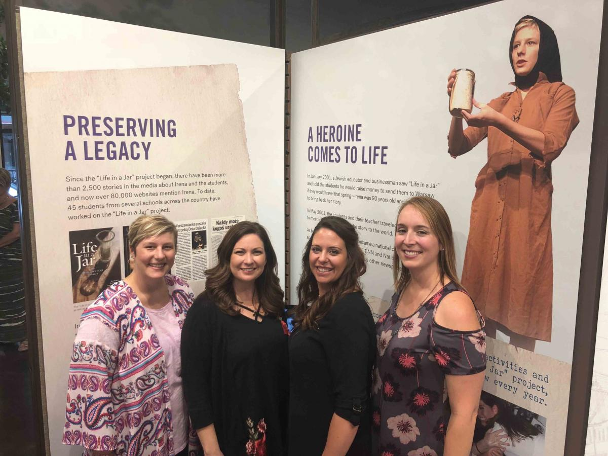 "The original three students—Liz, Megan, and Sabring—are joined by Jessica Shleton-Ripper (third from left), who performed many times with Life in a Jar. Here they visit the Irena Sendler exhibit at the Lowell Milken Center for Unsung Heroes in Fort, Scott, Kansas, in 2018. They are standing in front of exhibit walls that say ""Preserving A Legacy"" and ""A Heroine Comes to Life""."