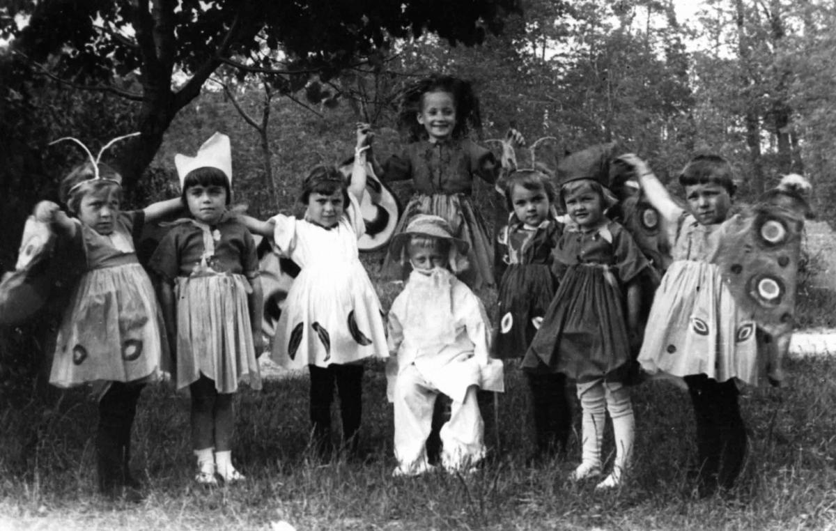 Black and white photo of children, in various costumes.
