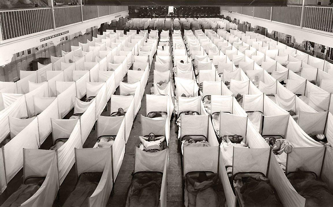 A naval hospital in New Orleans shows influenza victims filling out a massive grid of beds with modest partitions.
