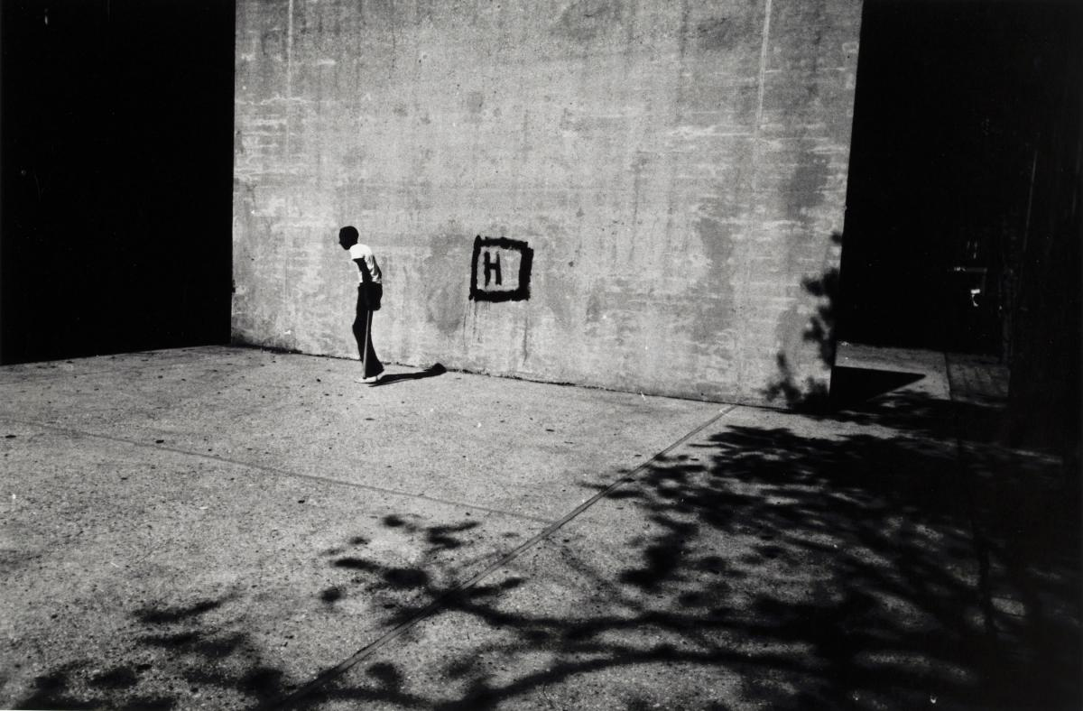 A thin boy holding a stickball bat in a handball court, the wall marked with a square and the letter H, as dark shadows bracket the image