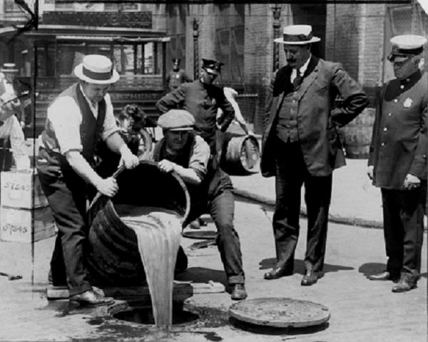 Prohibition agents pour liquor into sewer, 1921