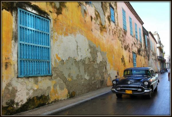Photo of a blue car in front of a yellow wall in havana, cuba