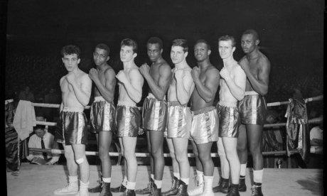 Boxers, possibly Golden Gloves contenders, lined up in boxing ring, c. 1955
