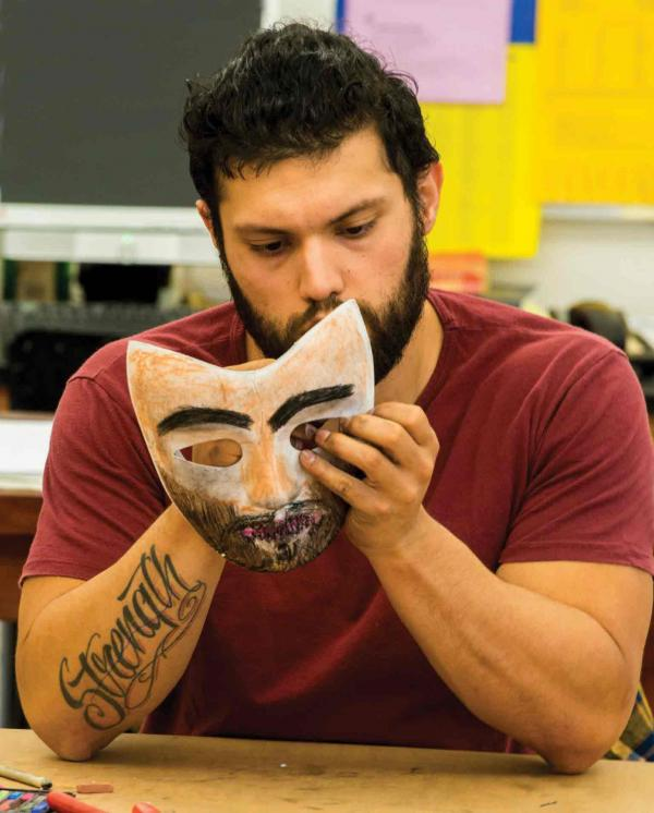 Veteran C. J. Villanueva paints a mask.