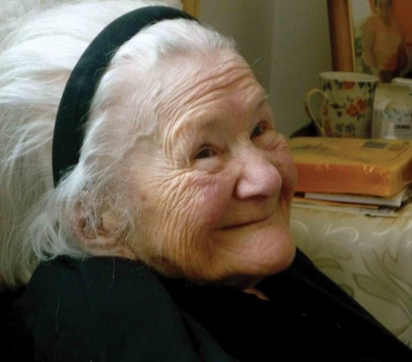Side portrait of Sendler with books and pots in the background. She is wearing black and a black headband.