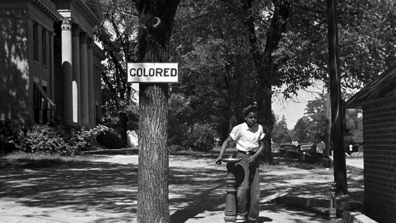 Black and white photo of an African American child at a segregated drinking fountain, 1938