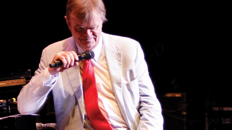 A portrait of Garrison Keillor in a white coat and khaki pants, holding a microphone.
