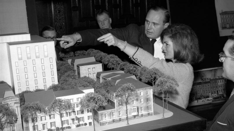 Black and white photo of Jacqueline Kennedy gesturing to an architectural model with a man