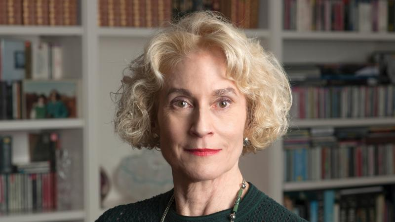 A portrait photo of Martha Nussbaum standing in front of a large bookcase.