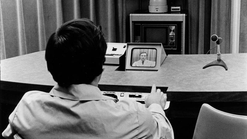 Photo of a man sitting at a desk looking at a small television screen, with a camera filming him in the background.