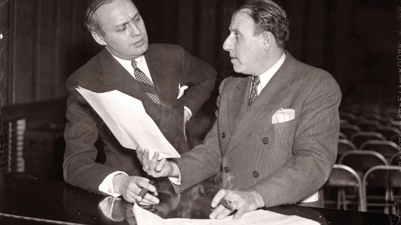 Black and white photo of Jack Benny and Harry Conn discussing what seems to be a contract
