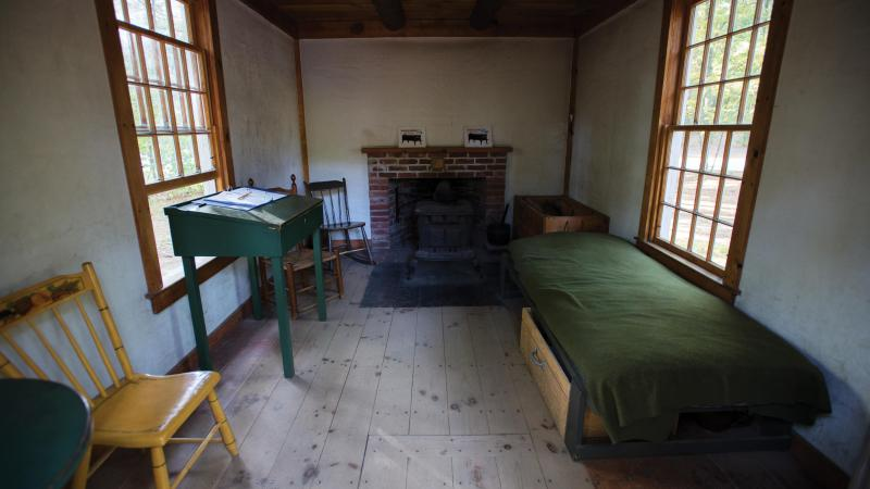 Picture of a basic bedroom with a fireplace, cot, and writing desk.