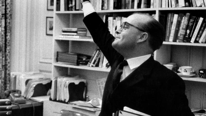 A black and white photo of Truman Capote waving his hand in the air in front of a bookshelf.