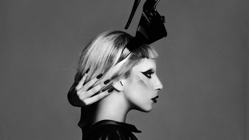 Side profile of Lady Gaga, wearing a black sculptural headdress, reaching her hand around the back of her neck